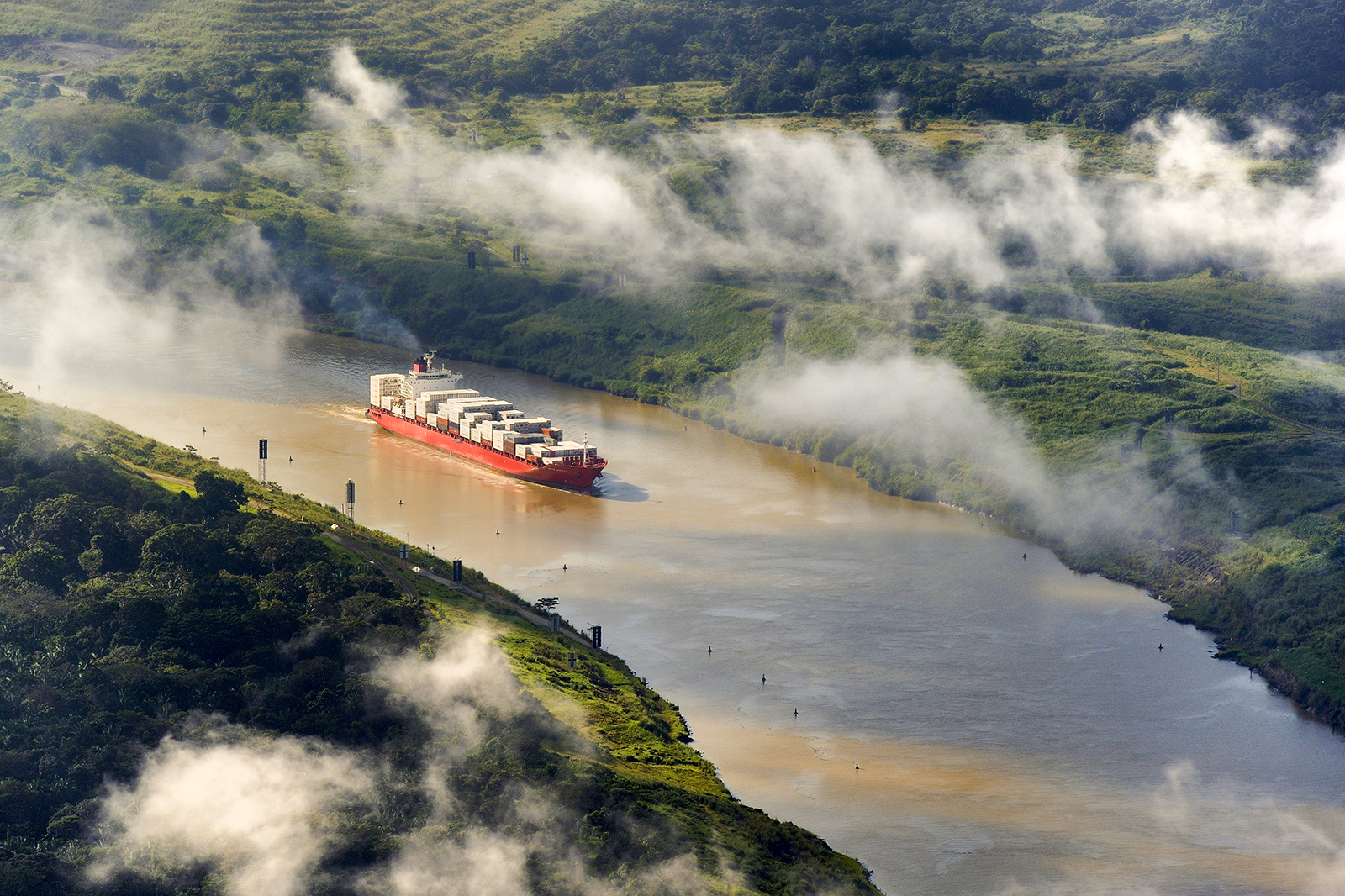 Panama, Panama Canal, a Panamax container cargo uses the Gaillard cut (or Culebra cut) between the Pedro Miguel locks on the Pacific side and the Chagres river leading to Gatun Lake (aerial view)